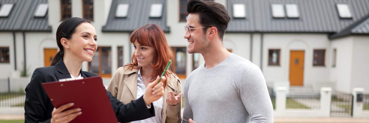 Immobilienmakler beim Verkaufsgespräch mit einem Paar